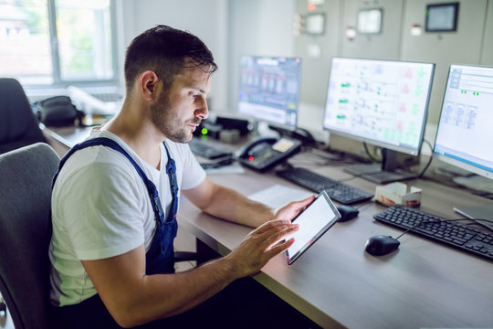 Serious caucasian unshaven factory worker in overall sitting in control room and using tablet.