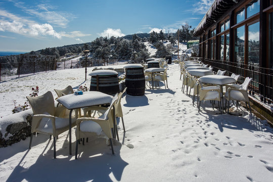 Terrace of a bar after a snowfall with tables and chairs completely covered with snow