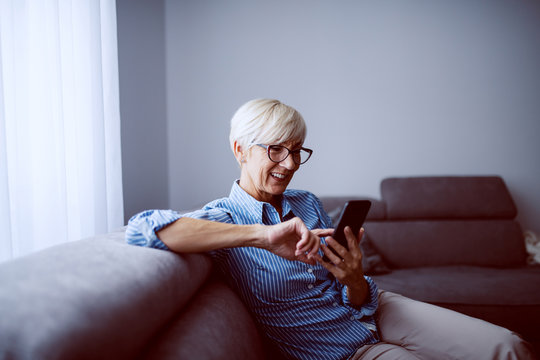 Attractive smiling caucasian blond senior woman with short hair sitting on sofa in living room next to window and using smart phone.