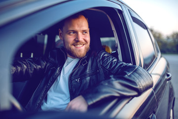 Young handsome smiling bearded blond caucasian man in leather jacket posing in his modern car.