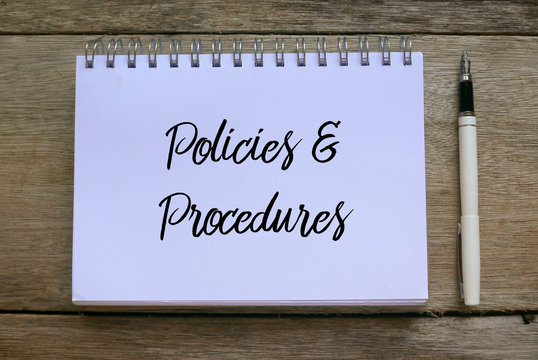 Top view of pen and notebook written with Policies and Procedures on wooden background.