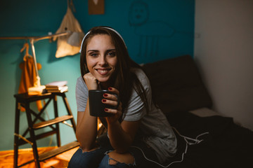 young woman student sitting on bed in her room drinking coffee