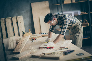 Fototapeta Profile side view portrait of his he nice attractive focused skilled experienced hardworking guy self-employed builder carving wood on table desk at modern industrial loft brick style interior indoors obraz