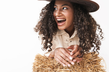 Beautiful smiling young african cowgirl sitting on a haystack