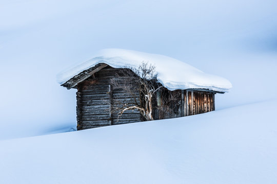Lonely wooden cabin in the swiss alps surrounded by snow at sunset