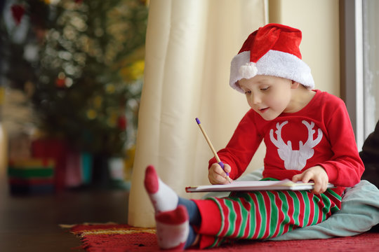 Little boy writing the letter to Santa. Child dreams of a gift that he can receive.