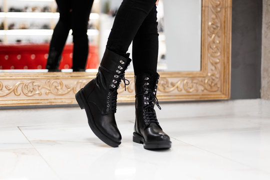 Closeup of female legs in fashionable leather black boots on lace-up in vintage jeans indoors. Stylish girl in trendy shoes stands on the tile near the mirror in the store. Autumn-spring casual style.