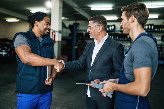 Happy manager handshaking with auto mechanic in a repair shop.