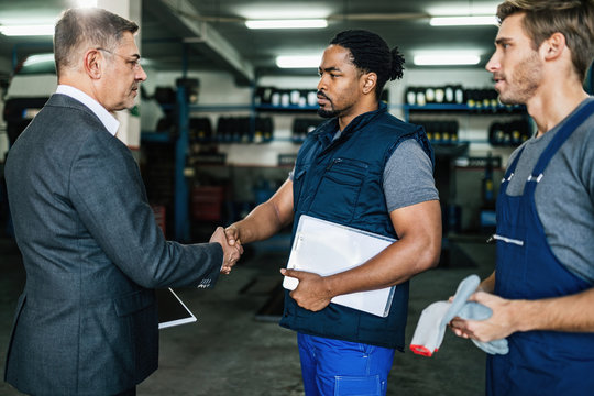 African American car mechanic shaking hands with a manager in auto repair shop.
