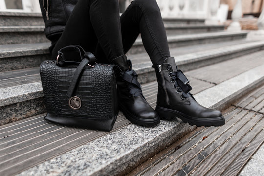 Young woman sits on stone steps outdoors in jeans in black fashion boots with a stylish leather handbag. Сlose-up of female legs in fashionable shoes with a trendy bag. Autumn winter collection.
