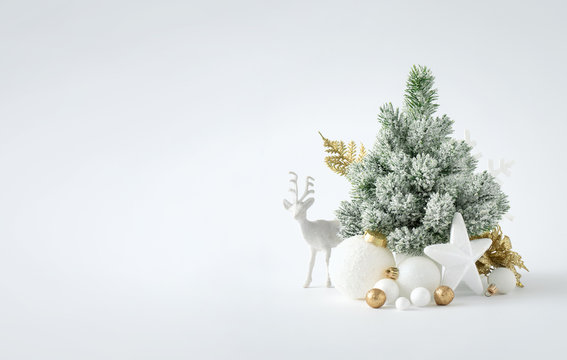 Christmas or New Year layout with white snowy Christmas tree and golden Christmas decoration. Bright  Holiday background.