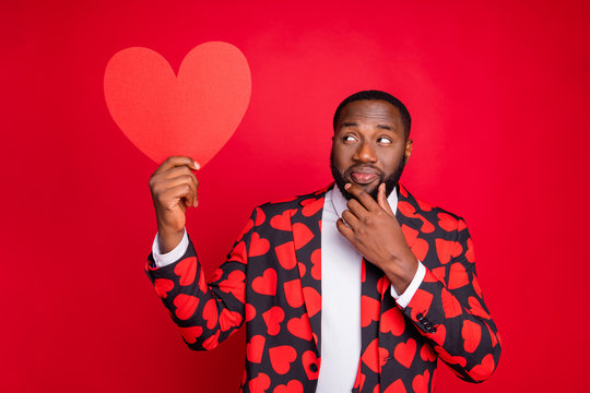 Photo of funny dark skin man cupid hold big paper heart thinking over creative way of love confession wear hearts pattern suit shirt necktie tie isolated red color background