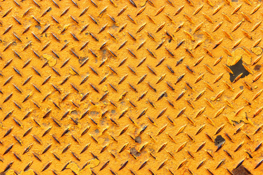 Rough painted yellow diamond plate background texture with some rust