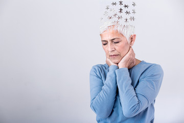 Memory loss due to dementia. Senior woman losing parts of head as symbol of decreased mind function. Senior woman losing parts of head feeling confused as symbol of decreased mind function. Wall mural