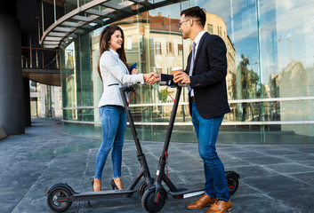 Two business people with electric scooter talking outside in front of modern business building.