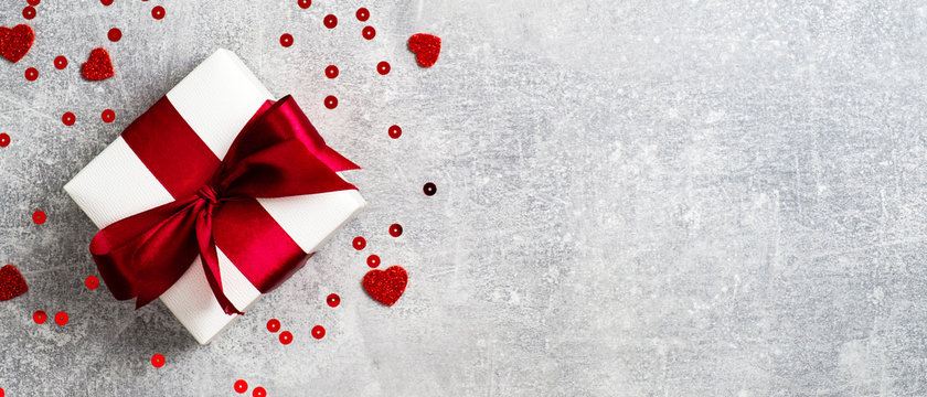 Valentines Day banner. White gift box with red ribbon on stone background decorated heart shaped confetti. Flat lay, top view. Love and romance concept.