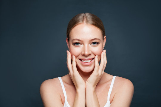 Beautiful woman face on blue background. Happy woman model smiling