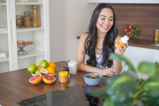 Young woman taking a nutritional supplement at breakfast