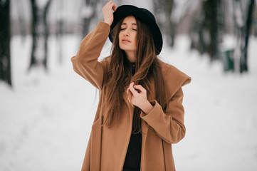 Closeup portrait of beautiful long haired brunnette girl with georgian appearance posing in brown jacket in winter park