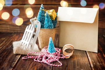 Artificial little Christmas treees in biodegradable peat moss, craft envelope, small sledge and wooden shavings.