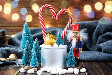 Christmas marshmallows, nutcracker and new year decorations on wood with grey plaid. Winter holidays