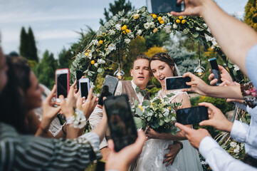 Friends take pictures of the ceremony and emotions of the newlyweds on a variety of phones and smartphones. Wedding portrait of the groom, bride and guests in the park.