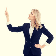 Happy smiling businesswoman in confident style black suit, showing something, some product or blank copy space for advertise slogan or text message. Caucasian blond model in business success concept.