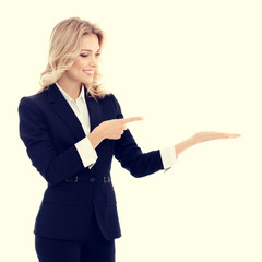 Happy smiling young businesswoman in confident style black suit, showing something, some product or copy space for advertise slogan or text message. Caucasian blond model in business success concept.