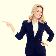 Happy smiling businesswoman in confident style black suit, showing something, some product or copy space for advertise slogan or text message. Caucasian blond model in business success concept.