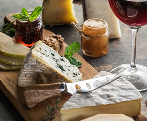 Wall Mural - Cheese platter with organic cheeses, fruits, nuts and wine on stone background. Tasty cheese starter.