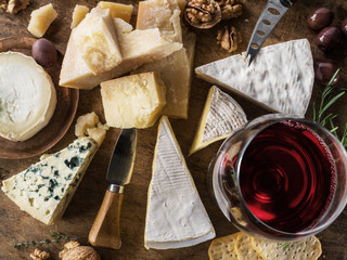 Wall Mural - Cheese platter with organic cheeses, fruits, nuts and wine. Top view. Tasty cheese starter.