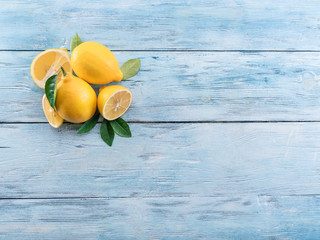 Wall Mural - Ripe lemons and lemon leaves on blue wooden background. Top view.