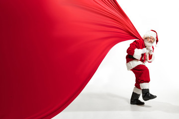 Santa Claus pulling huge bag full of christmas presents isolated on white background. Caucasian...