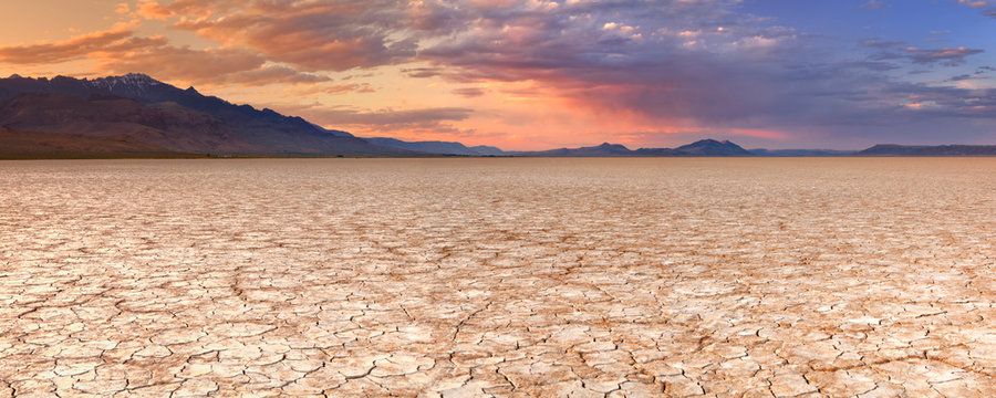 Cracked earth in remote Alvord Desert, Oregon, USA at sunset