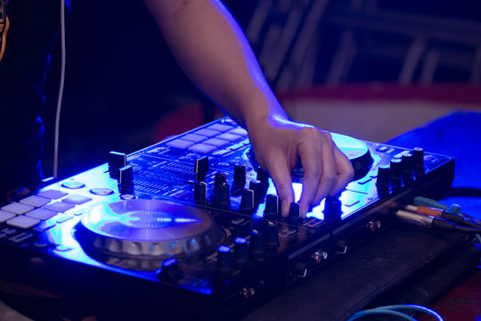 Sound engineer on mixer, close up of DJ hands on stage mixing, disc jockey and mix tracks on sound mixer controller, playing music at bar, disco tech or night club party.