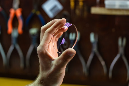 ophthalmologist hands close up, showing a glass lens for spectacles. Blurred background. Ophtalmologist equipment. Vision correction concept.