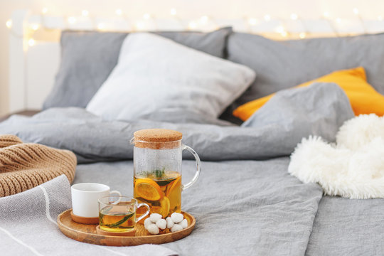 Cozy winter home decor: glass teapot and two cups of citrus tea with orange, lemon and mint on a wooden tray, bed with grey linen, blanket, pillows, plaid, led garland light. Breakfast in bed.