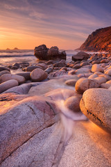 Rocky beach at sunset, Porth Nanven, Cornwall, England