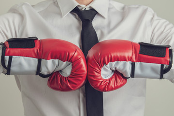 Businessman wearing red boxing bumping his fists together