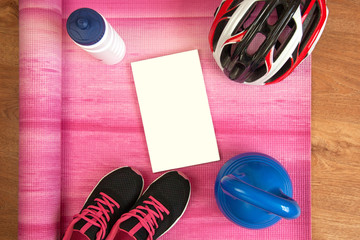 Healthy lifestyle items - sneakers, water bottle, cycling helmet, kettlebell, yoga mat with a blank motivational message poster on a bright pink background