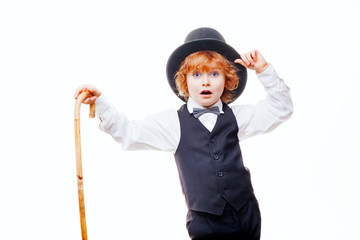kid actor in the theatre, stylish boy in hat isolated on white background, happy child actor with a cane in his hand dressed in a black suit, talented red curly boy playing in the theatre