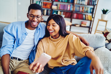 Cheerful dark skinned hipster couple making funny faces posing for selfie and using smartphone app, happy african american girl and guy sitting on sofa spending time at home making picture together.