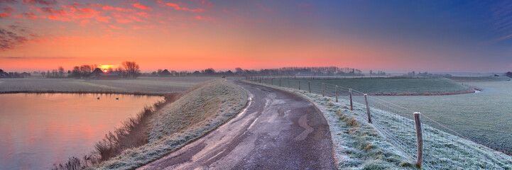 Fototapete - Typical Dutch landscape with a dike, in winter at sunrise