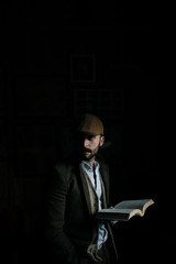 Portrait of a young man reading a book in suit