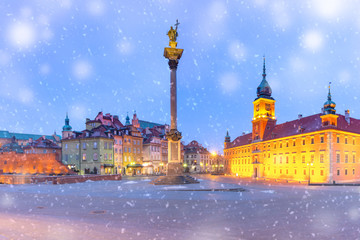 Castle Square with Royal Castle, colorful houses and Sigismund Column in Old town during snowy...