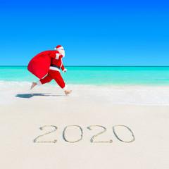 Santa Claus run at sandy ocean beach 2020 with Christmas sack