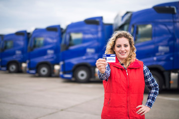 Woman truck driver proudly holding commercial driving license. In background parked trucks. Driving school and job openings for new drivers.
