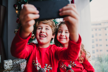 beautiful brother and sister at home taking a selfie with mobile phone. Happy kids sitting by the christmas tree