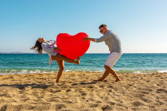 Young couple having fun on the beach with a big heart balloon. Summer love concept.