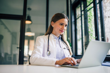 Obraz Positive doctor working on laptop in medical office, portrait. - fototapety do salonu